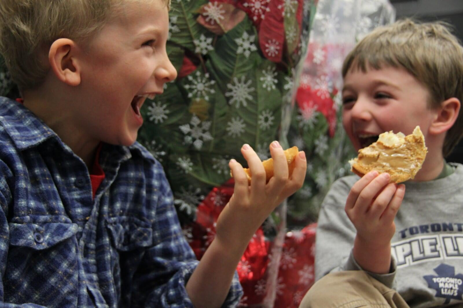 Two boys sitting laughing eating bagels in front of red packaged poinsettias.